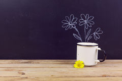 Coffee cup on wooden table over chalkboard background with hand drawing flowers. Royalty Free Stock Photography