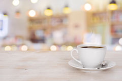 Coffee cup on wooden table over defocused cafeteria background.  Royalty Free Stock Image