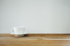 Coffee cup on wooden table over white background. Vintage tone stock photo