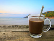 Coffee cup on a wooden table with the sea in the morning. Royalty Free Stock Photo