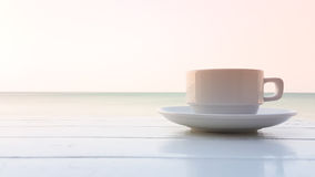 Coffee cup on the wooden table with sunflare Stock Photos