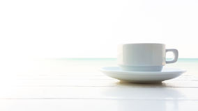 Coffee cup on the wooden table with sunflare Stock Image