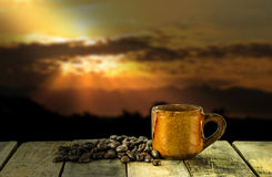 Coffee cup on wooden table and sunset background Stock Image