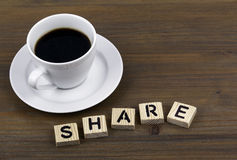 Coffee cup on a wooden table and text - SHARE Royalty Free Stock Photography