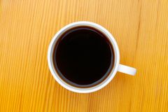 Coffee cup on wooden table of yellow color - shot from above Royalty Free Stock Photo