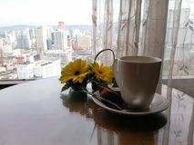 Coffee break. Coffee cup and yellow daisies on a small table by a curtained window overlooking cityscape Royalty Free Stock Images