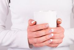 Beautiful woman hands with french nails manicure holding coffee cup. Coffee cup in young woman hands with french nails manicure. Close up. Beauty and Drink Royalty Free Stock Photography