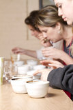 Coffee Cupping Cups. Three women taste and compare brewed coffees at a cafe. Process is known as Coffee Cupping. focus is on coffee crusted cups Royalty Free Stock Images