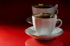 Coffee in cups. Two cups of coffee on a red-black background Royalty Free Stock Photography