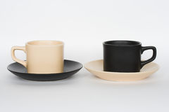 Coffee cups. Two coffee cups opposite each other - beige and black, with changed saucers, isolated on white Royalty Free Stock Photography