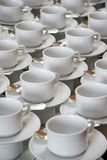 Coffee cups. Stacks of coffee cups on saucers with silver teaspoons Royalty Free Stock Image