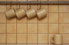 Coffee cups. Four coffee cups hanging in a row and one standing below Stock Image