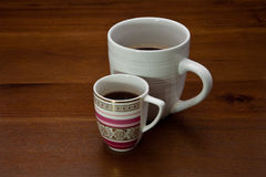 Coffee cups. Two coffee cups on a wooden background containing coffee Royalty Free Stock Photo