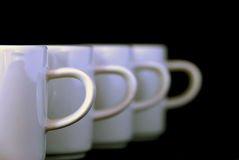 Coffee cups. Four white coffee cups or mugs in raw - against black background Royalty Free Stock Image