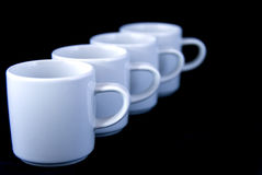Coffee cups. Four white coffee cups or mugs in raw - against black background Stock Photos