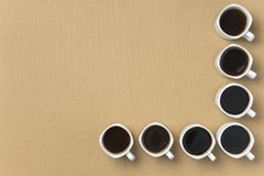 Coffee cups arranged in the angle of a light brown background Royalty Free Stock Photo