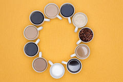 Coffee Cups Arranged in Circle Isolated on Yellow Royalty Free Stock Photos