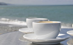 Coffee cups and beach. Coffee cups on table with beach and sea in background Stock Photos