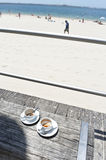 Coffee cups on beach. Two empty coffee cups on a table near a sandy beach. Copyspace Royalty Free Stock Images