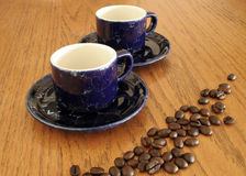 Coffee Cups and Beans. Two blue coffee cups on table with coffee beans on table Stock Photo