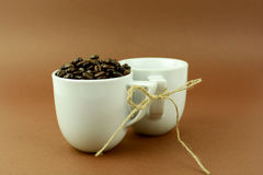 Coffee cups with a bow and coffee beans brown background.  Royalty Free Stock Images