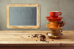 Coffee cups and chalkboard on wooden table Royalty Free Stock Photo
