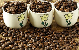 Coffee cups with coffee beans. On the background Royalty Free Stock Images
