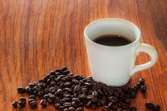 Coffee cups and coffee beans on wooden boards. Coffee in cups and coffee beans on wooden boards stock photo