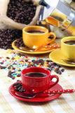 Coffee cups with coffee maker. Red cup of coffee in the foreground with coffee maker  and other cups with background out of focus Royalty Free Stock Images