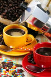 Coffee cups with coffee maker. Red coffee cup and yellow cup with jute sack and coffee maker on colorful background with colored sugar pearls Royalty Free Stock Photos