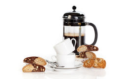 Coffee Cups and Cookies. Two stacked white coffee cups on saucers and two spoons surrounded with various cookies, filled french press carafe in background Stock Image