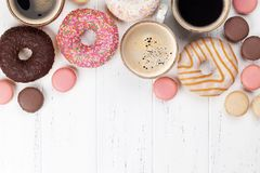 Coffee cups, donuts and macaroons Stock Image