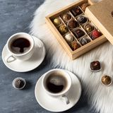 Coffee cups and fine chocolate candies. Collection of homemade truffles in gift box stock photo