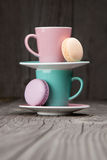 Coffee cups with french macaroons on wooden table Royalty Free Stock Photos