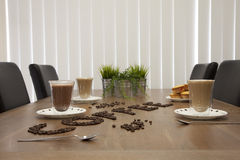 Coffee Cups Glass and Beans. Coffee beans spelling the word coffee, with clear coffee cups with a warm feel look Stock Photos
