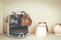 A Coffee cups hanging and dish under stock images