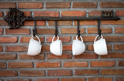 Coffee cups hanging on hooks Royalty Free Stock Images