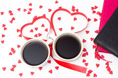 Coffee cups, large heart from red ribbon and lots of little hearts, pink and black diary on white background Royalty Free Stock Image