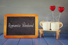 Coffee cups next to blackboard with text: ROMANTIC WEEKEND. Couple coffee cups next to blackboard with text: ROMANTIC WEEKEND on wooden table. vintage filtered Royalty Free Stock Image