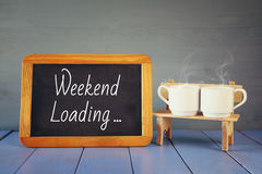 coffee cups next to blackboard with text: WEEKEND LOADING Royalty Free Stock Photo