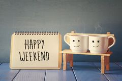 Coffee cups next to notebook with phrase happy weekend. Couple coffee cups next to notebook with phrase happy weekend on wooden table. vintage filtered Royalty Free Stock Images