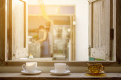 Coffee cups on opened wooden window pane with outdoor view Royalty Free Stock Photography
