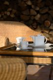 Coffee Cups And Pitcher On Patio. Pitcher and cups for coffee sitting on a table near patio furniture on an outdoor patio stock images