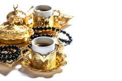 Coffee cups rosary beads white background Islamic holidays Ramad. Gold coffee cups and rosary beads on white background. Islamic holidays. Ramadan kareem Stock Photo