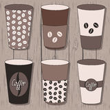 Coffee cups set. Coffee beans pattern. Design of coffee cups on wood background Stock Photos
