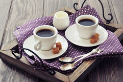 Coffee in cups. With spoon and milk on vintage wooden tray Royalty Free Stock Images