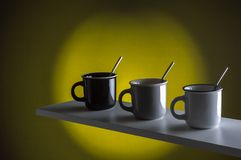 Coffee cups with spoon on yellow background royalty free stock photos