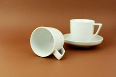 Coffee cups standing and laying on brown background Stock Photos