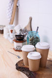Coffee cups for take away, various sizes, and kitchenware on wooden lunch counter. Stock Image