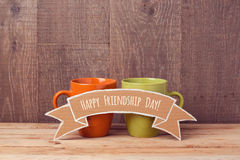 Coffee cups on wooden table with cardboard banner. Friendship day celebration Stock Photography